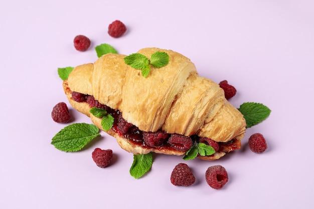 Croissant with raspberry jam on purple ãƒâ¢ã'â€ã'â‹background