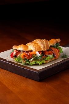 テキスト用のコピースペースのある木製のテーブルにサーモンとクリームチーズのクロワッサン。