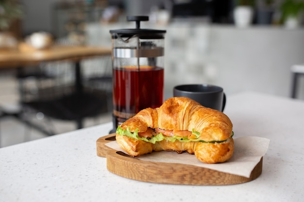 Croissant with salmon and fresh salad is served on a wooden board for lunch. black tea in a teapot. fitness food in a cafe.
