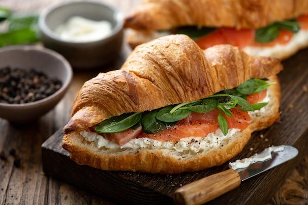Круассан с лососем, шпинатом и сливочным сыром на деревянной доске, выборочный фокус, крупный план