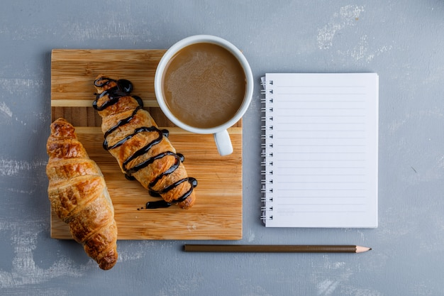 Croissant with sauce, coffee, notebook, pencil on plaster and wooden board, flat lay.