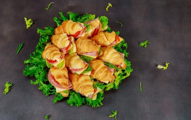 Круассан с колбасным сыром и зеленью. на темном фоне