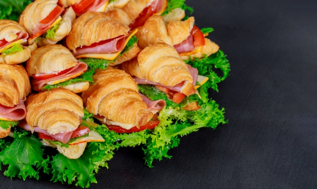 Croissant with sausage cheese and herbs on dark background