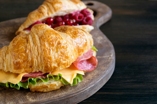 Croissant with sausage cheese and herbs. on dark background
