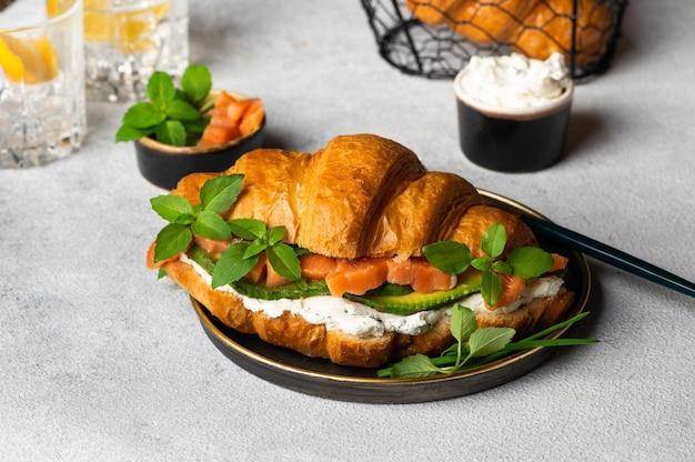 Круассан с копченым малосольным лососем, шпинатом и рукколой подается на черной тарелке. закройте вверх. здоровый французский завтрак. морепродукты и сыр