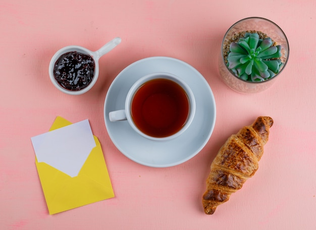 Croissant with tea, jam, card in envelope, plant on pink table, flat lay.