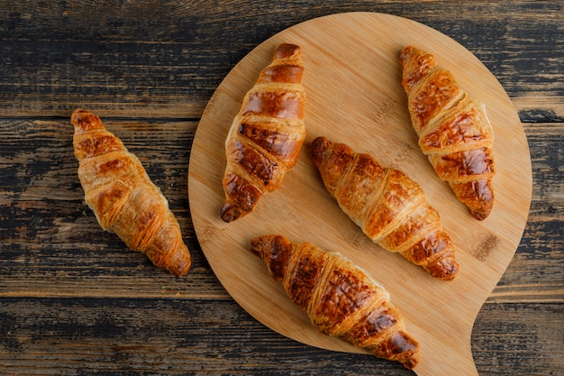 Croissant on wooden and cutting board. flat lay.