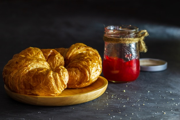 Croissant on wooden dish and strawberry jam bottles