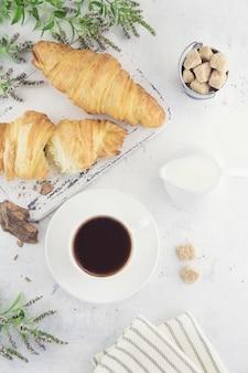 Круассаны, чашка кофе с кусочком натурального шоколада