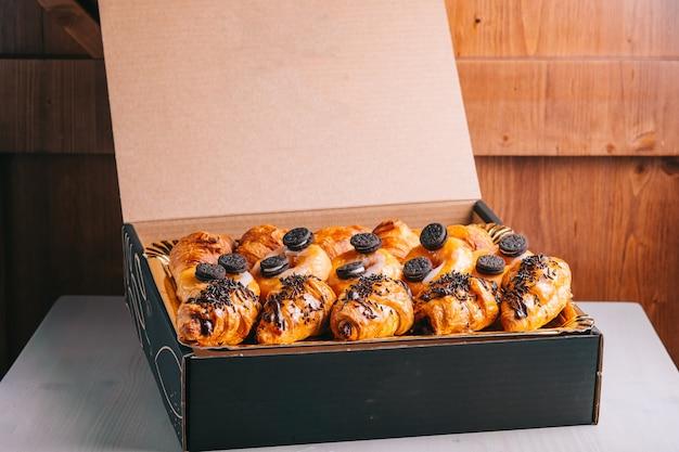 クロワッサンとチョコレートドーナツの食品配達甘いスナックを箱に入れて