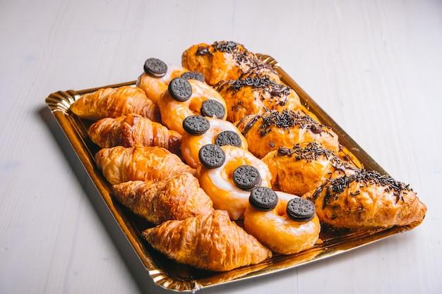 テーブルの上の朝食の甘い軽食のためのクロワッサンとチョコレートドーナツ