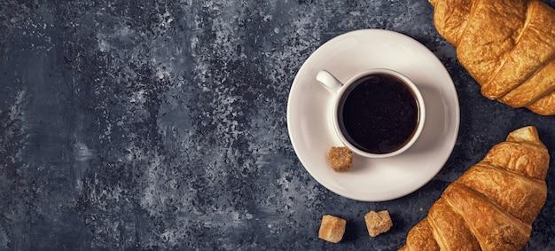 Круассаны и кофе на темном столе