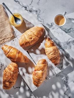 白いテーブルの上のクロワッサンとコーヒー