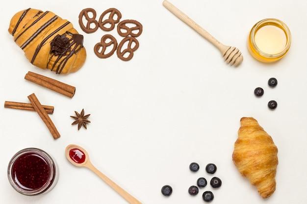 クロワッサンとクッキー、ベリー、アプリコットのハチミツ、ジャム、シナモン。栄養価の高い朝食用の製品のセット。白色の背景。フラット横たわっていた。コピースペース
