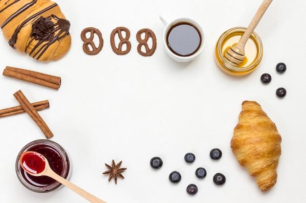 クロワッサンとクッキー、ベリー、アプリコットのハチミツ、ジャム、シナモン。栄養価の高い朝食用の製品のセット。白色の背景。フラットレイ