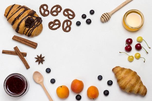クロワッサンとクッキー、ベリー、アプリコットのハチミツ、ジャム、シナモン。栄養価の高い朝食用の製品のセット。