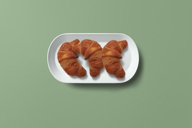 朝食のコンセプトのためにクロワッサンを皿に盛り付けます