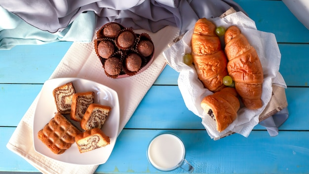 Croissants, chocolate pralines and vanilla pie on the blue table.