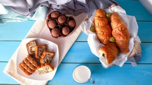 Cornetti, praline al cioccolato e torta alla vaniglia sul tavolo blu.
