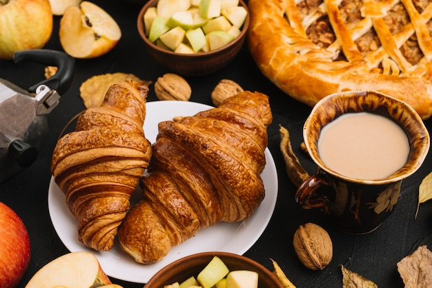 Croissants and coffee near apples and pie