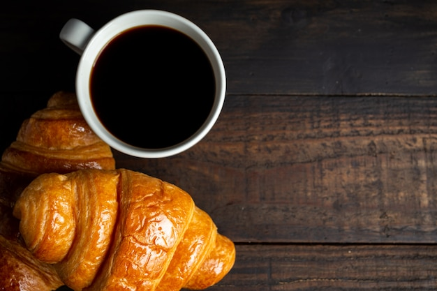 Croissants and coffee on old wood table.