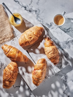 Croissants and coffee on white table
