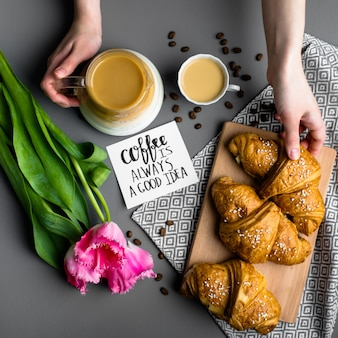 Croissants cup of coffee and a bouquet of tulips