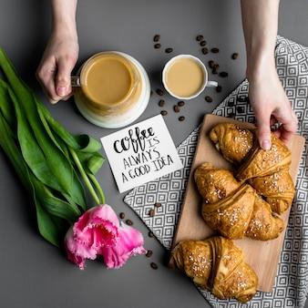 クロワッサン一杯のコーヒーと花束