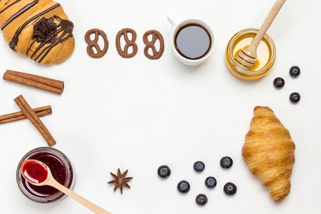 Croissants and figured cookies, berries, apricots honey, jam, cinnamon. set of products for nutritious breakfast. white background. flat lay