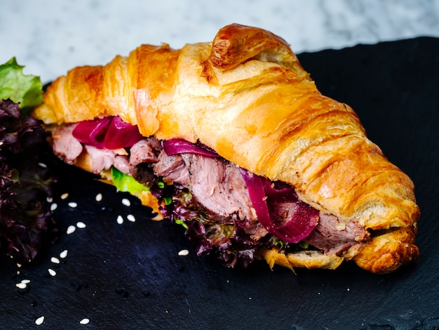 Croissants filled with sliced meat and herbs