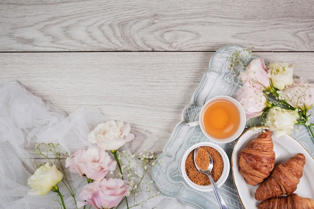 Croissants and flowers in flat lay