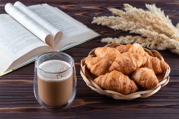 Croissants and a glass of coffee with milk on dark brown wooden table