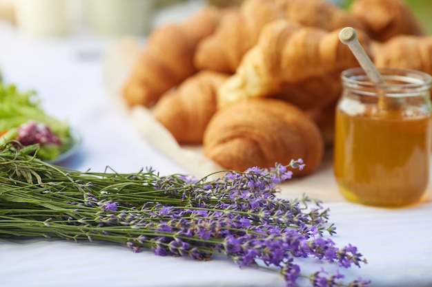 Croissants and honey on table in lavender field