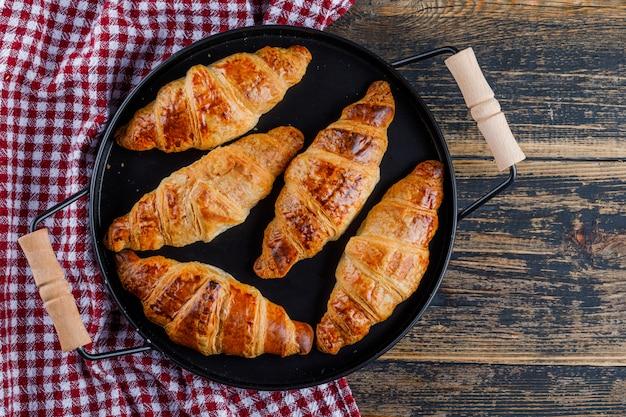 Круассаны на сковороде на деревянном и кухонном полотенце. плоская планировка