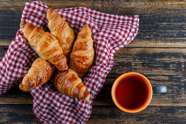 Круассаны на сковороде с полотенцем с чашкой чая лежали на деревянном столе