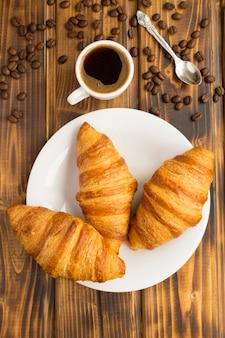 白い皿にクロワッサン、茶色の木製テーブルのカップにブラックコーヒー。上面図。