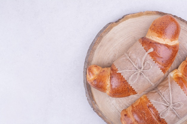 Круассаны, изолированные на деревянном блюде на серой поверхности