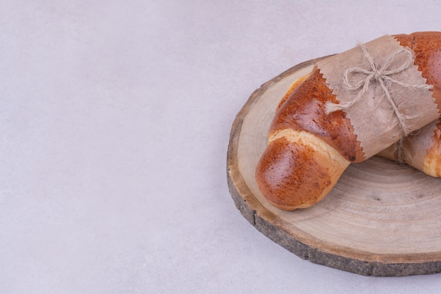 Croissants isolated on a wooden platter on grey surface