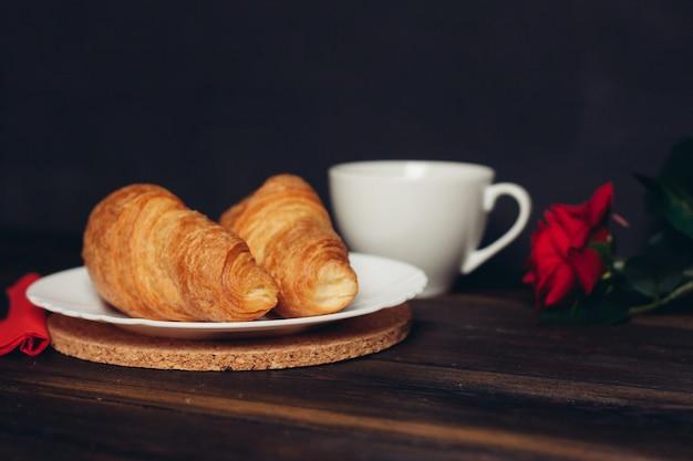 プレートとコーヒーのカップにクロワッサン赤いバラ木製テーブル