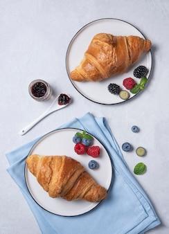 Круассаны на тарелках с ягодами на сером фоне
