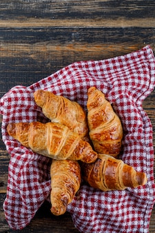 Croissants in a pan with towel on a wooden table. flat lay.