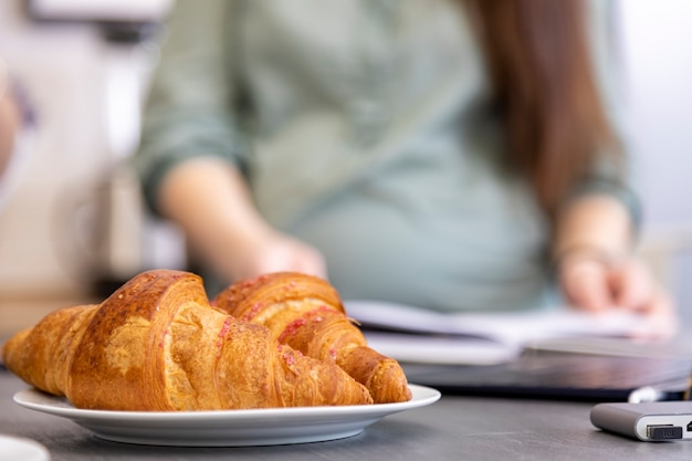 Croissants on plate on kitchen table silhouettes of pregnant woman reading book in blur