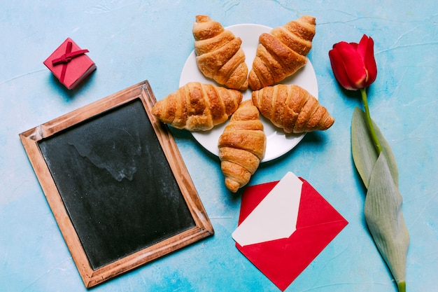 Croissants on plate with blank chalkboard