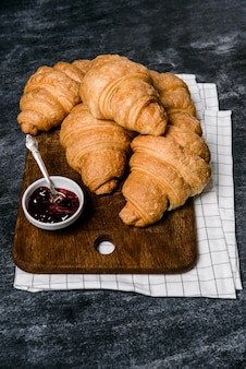 Croissants and pot with jam aside on grey table