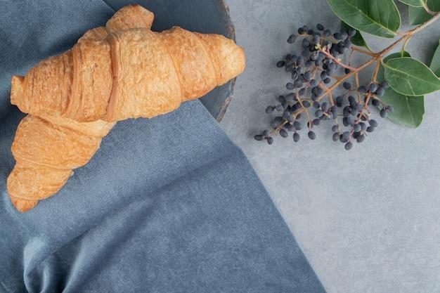 Croissant su un asciugamano con uva sul pavimento di marmo, sullo sfondo di marmo. foto di alta qualità
