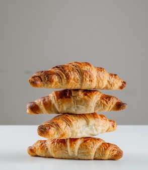 Croissants on white and grey table. side view.