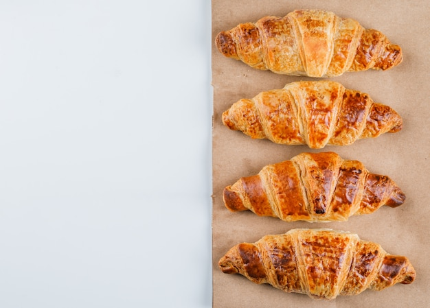 Croissants on white and paper bag, flat lay.