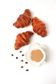 흰색 배경에 커피 한 잔을 곁들인 크루아상, 위쪽 전망, 사람 없음, 수평, . 고품질 사진