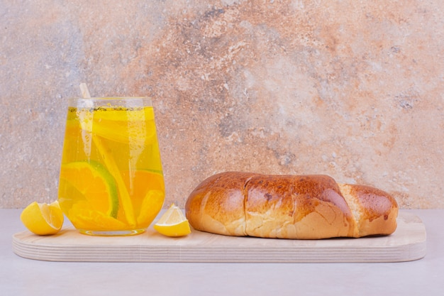 白い表面にレモネードのグラスが付いているクロワッサン
