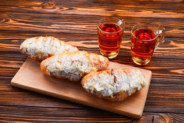 木製のテーブルにアーモンドとお茶とクロワッサン